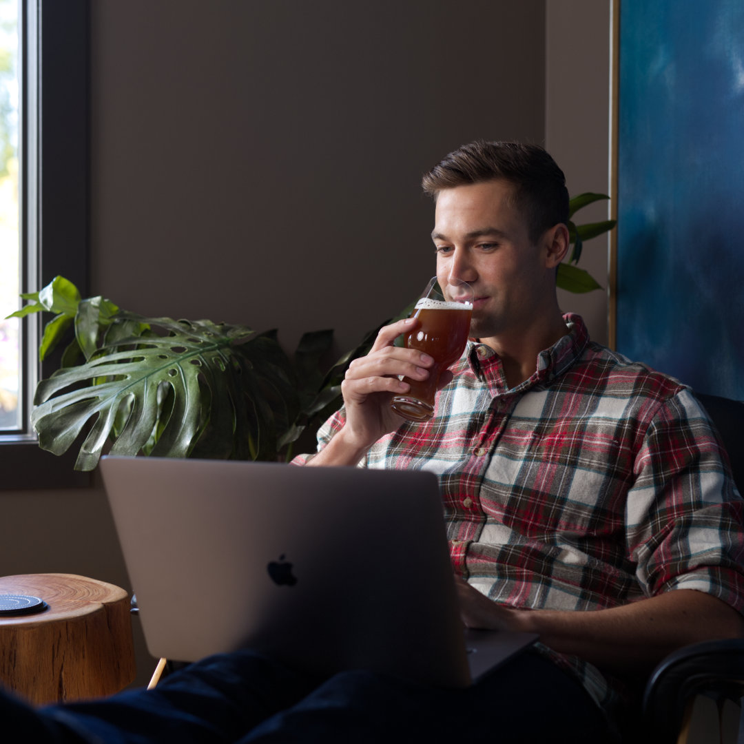 Man shopping online while drinking beer.