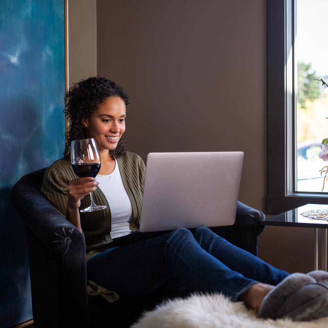 Woman lounging with a glass of wine while shopping online using her laptop.