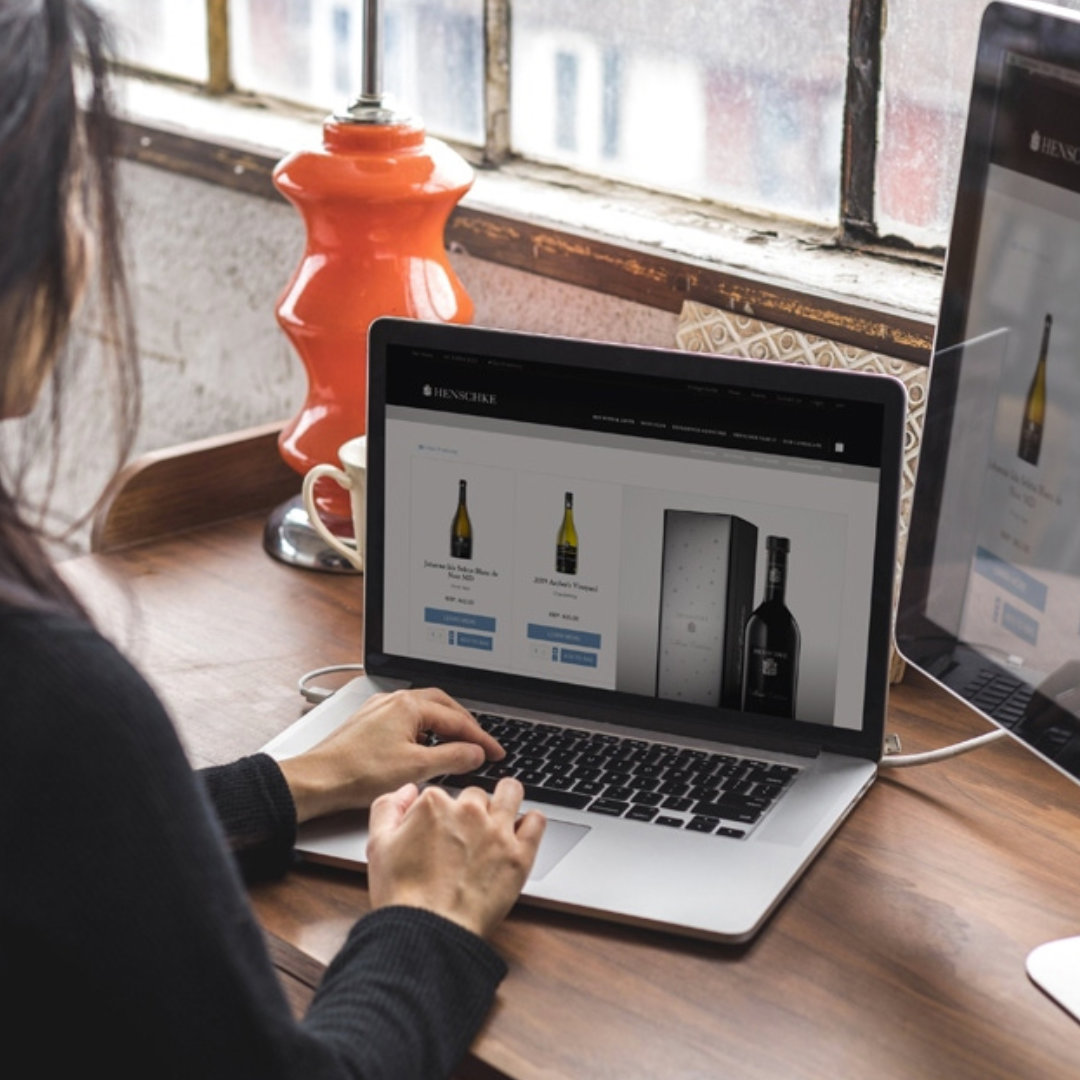 A woman using her laptop to shop online for wine.