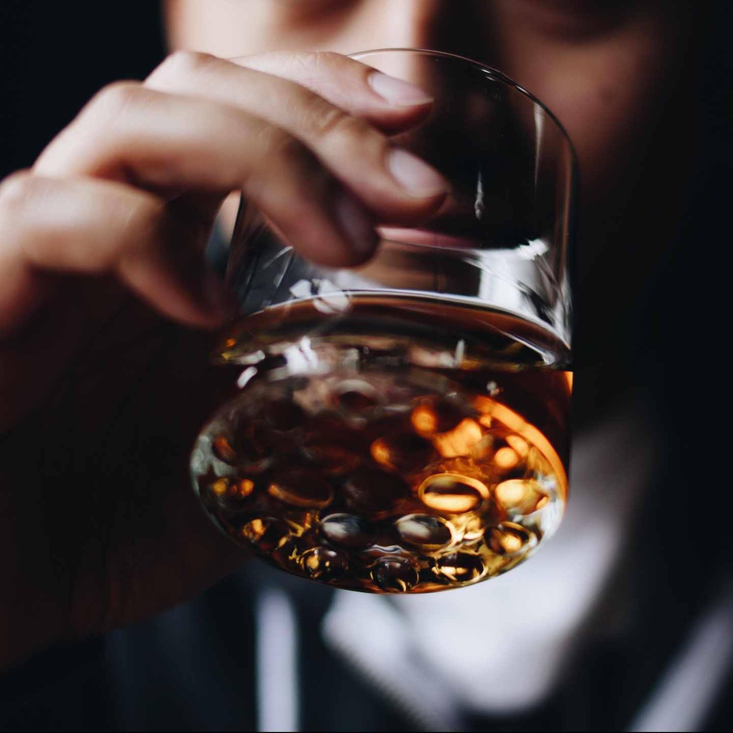 Close-up of glass of liquor being sipped.