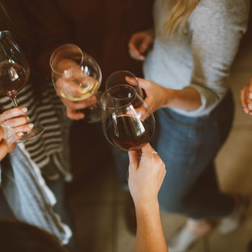 A group of people clinking wine glasses together to cheers
