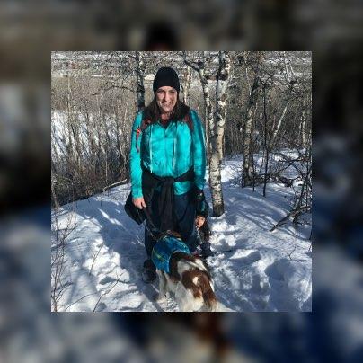 Bronwyn wearing a teal coat while walking her dog.