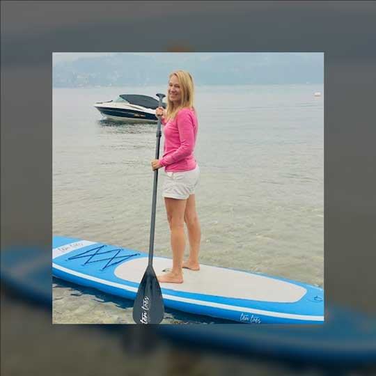 Christine standing on a paddle board.
