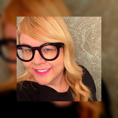 Jodi taking a selfie while wearing thick-rimmed black glasses.
