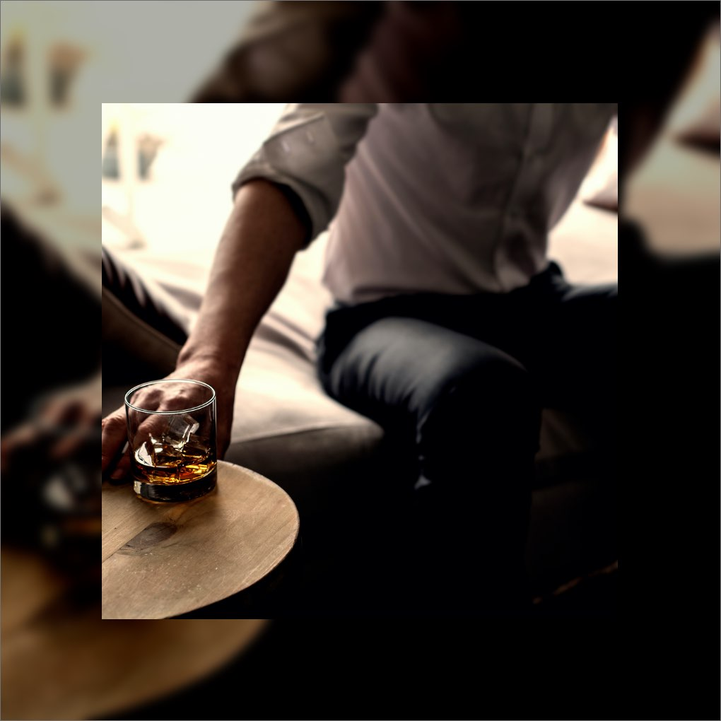 A man reaching for a glass of whiskey on the rocks.